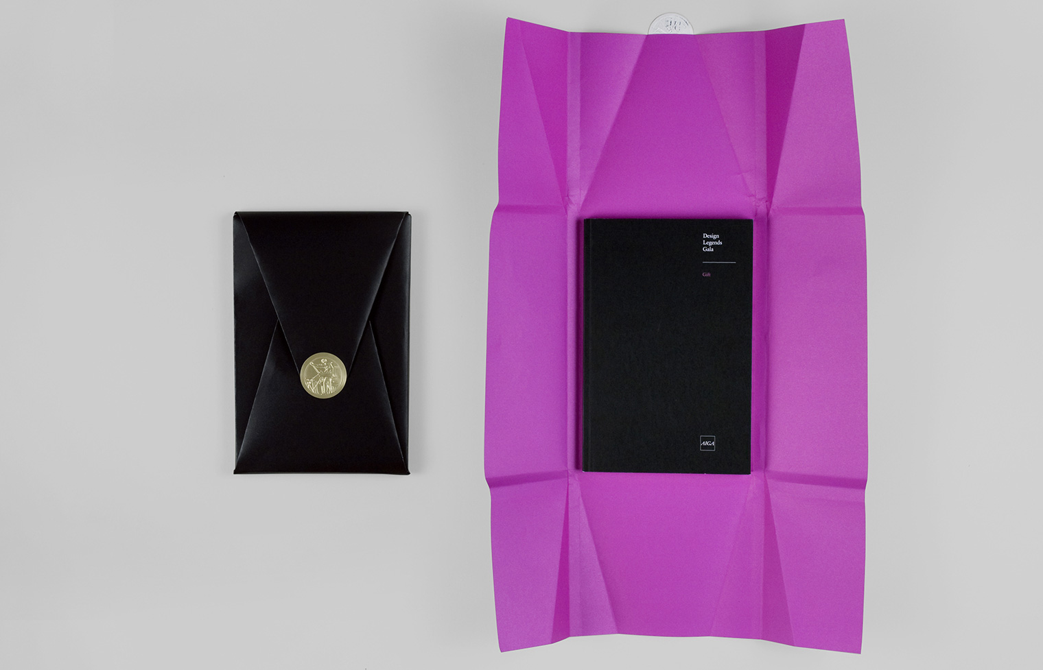 The commemorative book, wrapped in paper and closed with the AIGA seal and unwrapped. It is given to each Design Legends Gala attendee.